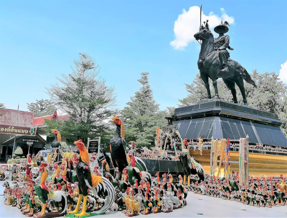Sur la gauche, une statue du roi Taksin le Grand à cheval, entourée de nombreux coqs, symbole de la réincarnation du roi.