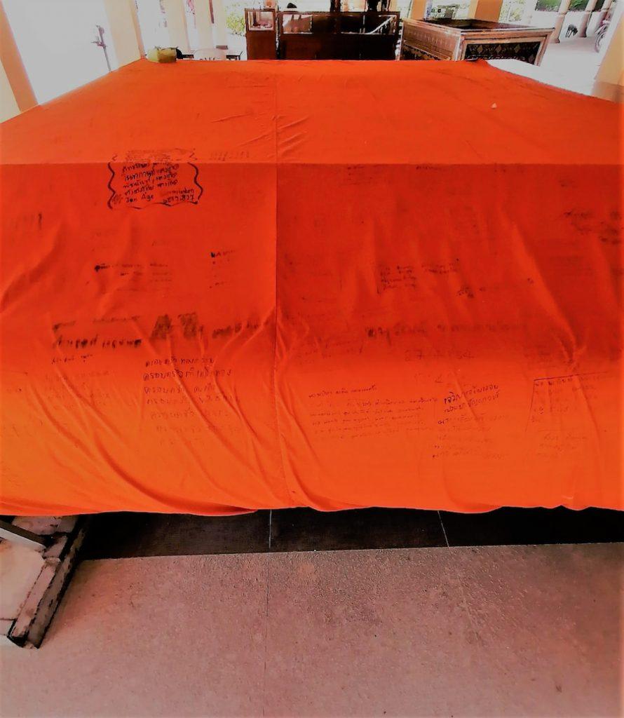 Les fidèles écrivent leurs souhaits et prières sur cette étoffe dont le moine sera drapé pendant certaines cérémonies