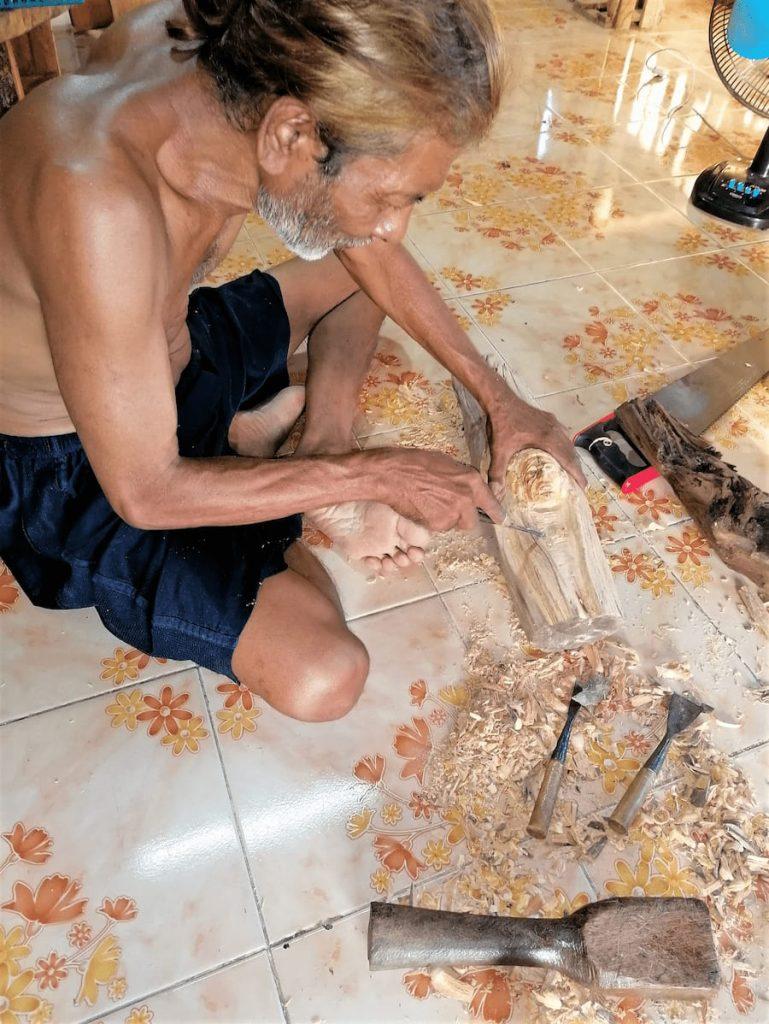 Il est assis par terre en train de sculpter un visage, mais s'arrête pour nous détailler toutes ses réalisations.